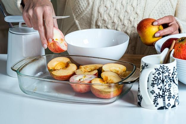 Kobieta wkłada ręcznie pokrojone jabłka do szklanej miski i przygotowuje je do wypieku domowego wypieku na święta