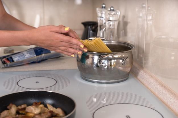Kobieta wkłada spaghetti do garnka z wrzącą wodą na płycie grzejnej podczas gotowania wieczornego posiłku