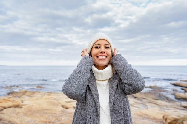 Kobieta wkłada wełniany kapelusz na głowę, uśmiechając się na zewnątrz w mroźnej zimie w nadmorskim kurorcie.