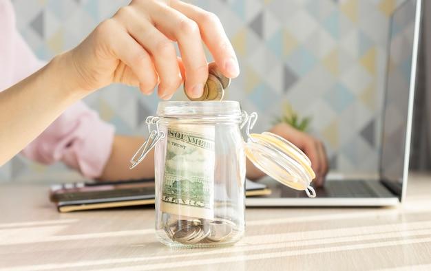 Kobieta, wkładanie pieniędzy do szklanego słoika przy stole, zbliżenie