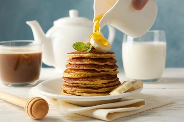 Kobieta wlać miód na naleśniki. słodkie śniadanie