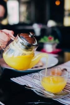 Kobieta wlać szklany czajniczek herbaty pionowe
