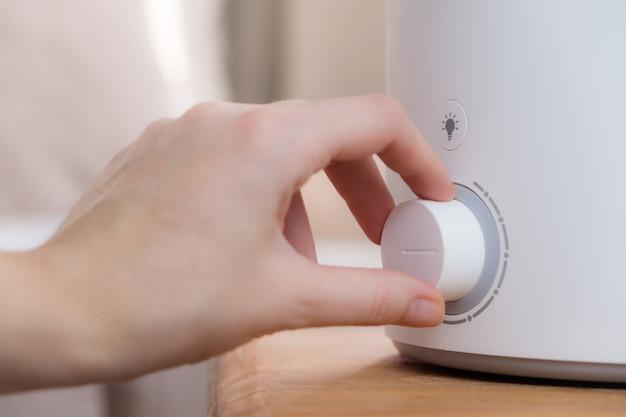 Kobieta włącza w domu nowoczesny nawilżacz powietrza, dyfuzor olejków aromatycznych