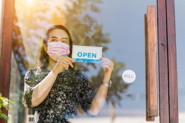 Kobieta, właścicielka firmy, otwiera kawiarnię i jedzenie, po tym, jak rząd złagodzi środki kwarantanny, aby zapobiec epidemii.