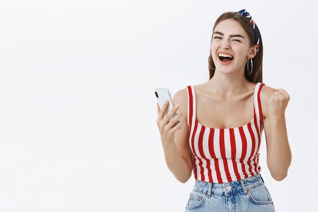 Kobieta, właścicielka sklepu internetowego, świętująca świetną ofertę online, trzymając smartfon zaciskający się w dłoni, pasuje do gestu sukcesu, krzyczącego tak, szczęśliwa i radosna świętuje zwycięstwo