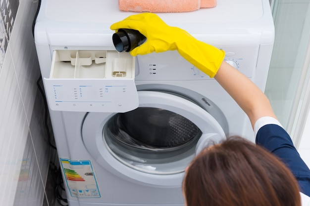 Kobieta wlewa płyn do zmiękczania tkanin do pralki rękami w rękawiczkach, gdy wykonuje prace domowe, widok z bliska pod dużym kątem