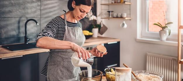 Kobieta wlewając cukier do szklanej miski