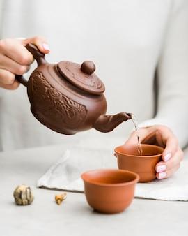 Kobieta, wlewając filiżankę herbaty z czajnik