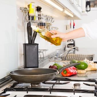 Kobieta wlewając olej na patelni nad kuchenką gazową
