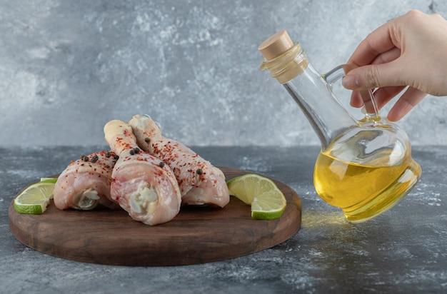 Kobieta wlewając olej świeże surowe udka z kurczaka.