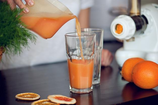Kobieta wlewanie świeżego soku pomarańczowego do szkła na stole w kuchni
