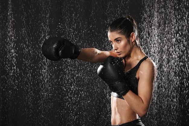 Kobieta wojownik 20s w odzieży sportowej i czarne rękawice bokserskie rzuca ciosy pod krople deszczu, odizolowane na ciemnym tle