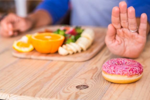Kobieta woli warzywa i owoce w różowym pączku - dwie opcje - na stole - w domu w domu - zdrowy styl życia i koncepcja