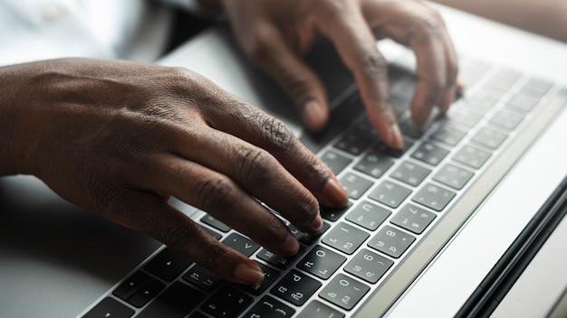 Kobieta wpisując na klawiaturze laptopa
