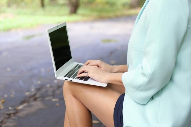 Kobieta wpisując na laptopie na zewnątrz z bliska