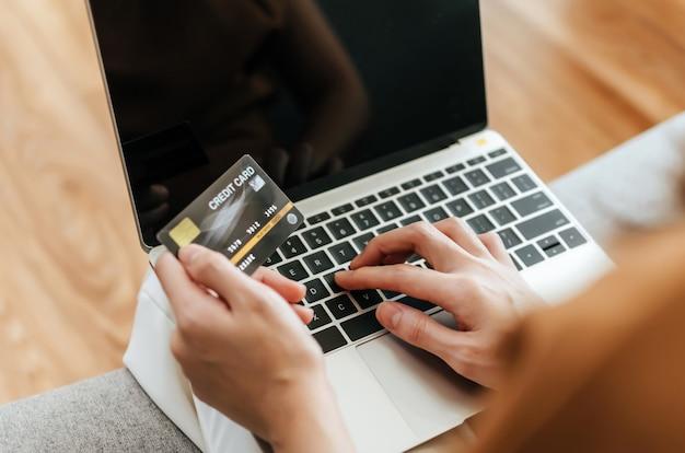 Kobieta wprowadzanie kodu na komputerze przenośnym i płacenie rachunku kartą kredytową na biurku w domowym biurze