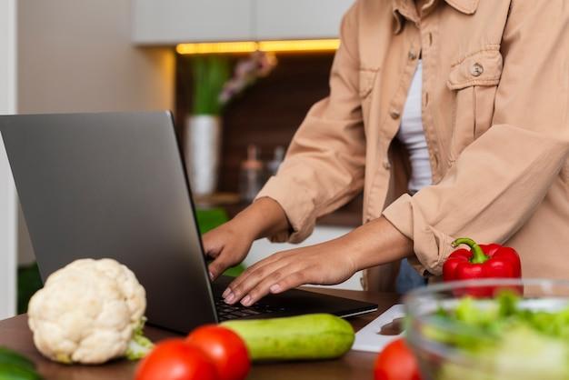 Kobieta wręcza działanie na laptopie w kuchni