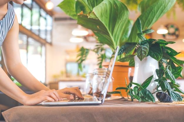 Kobieta wręcza działanie z laptopem w biurze.