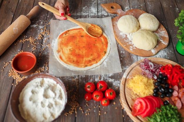 Kobieta wręcza kładzenie sos pomidorowy na cieście do pizzy