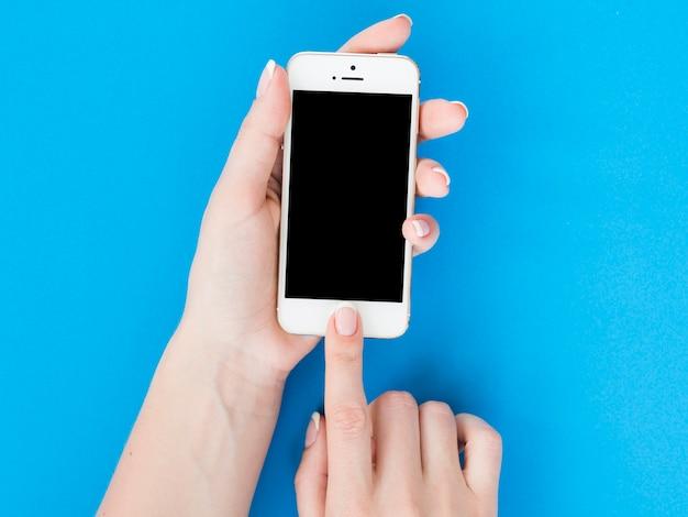 Kobieta wręcza mienia smartphone na błękitnym tle