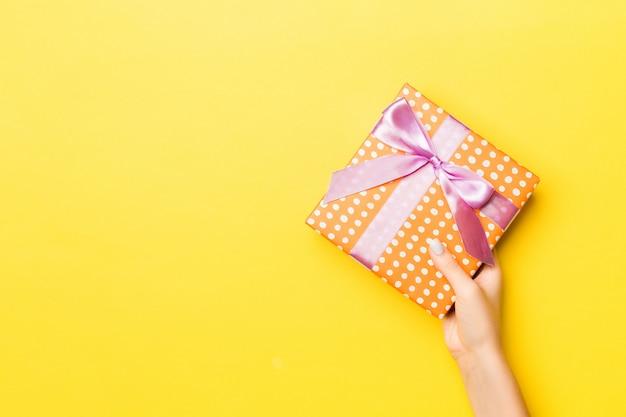 Kobieta wręcza mienie prezenta pudełko na barwionym tle