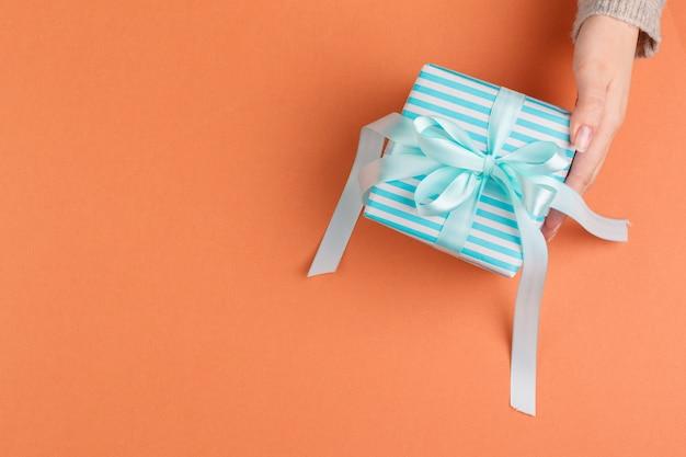 Kobieta wręcza mienie prezenta pudełko na pomarańczowym tle