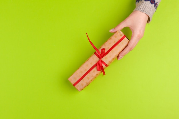 Kobieta wręcza mienie prezenta pudełko na zielonym tle