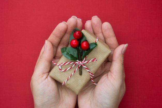 Kobieta wręcza mieniu bożenarodzeniowego prezenta pudełko z czerwonym faborkiem nad czerwonym tłem.