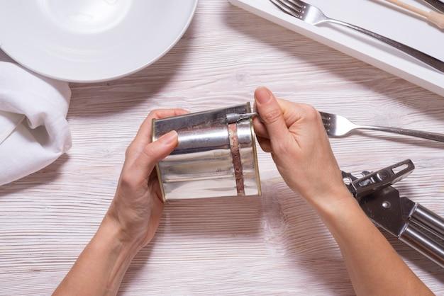 Kobieta wręcza otwieranie blaszaną puszkę z peklowaną wołowiną, odgórnego widoku kuchenny stół