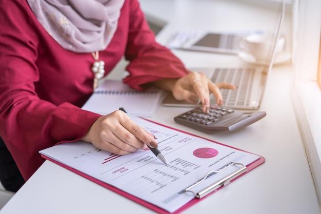Kobieta wręcza pracę z kalkulatorem o osobistym planowaniu finansowym w kawiarni.