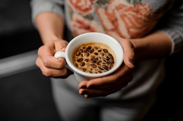 Kobieta wręcza trzymać białą filiżankę świeża i aromatyczna kawa