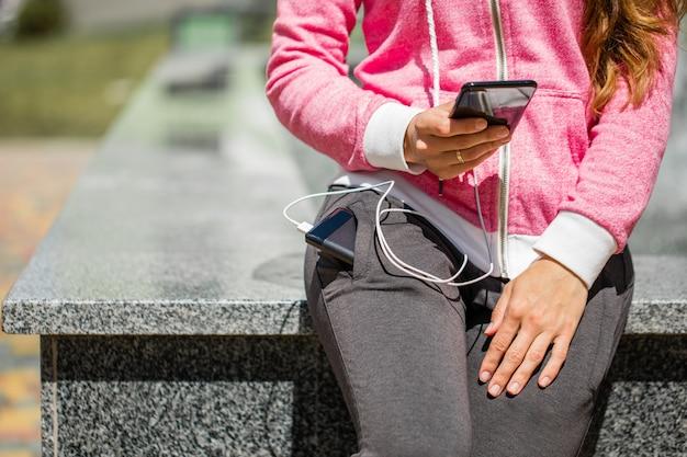 Kobieta wręcza trzymać czarnego smartphone ładuje baterię od zewnętrznego zasilania banka