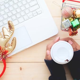 Kobieta wręcza trzymać filiżankę na stole z laptopem, bożenarodzeniowy zakupy pojęcie