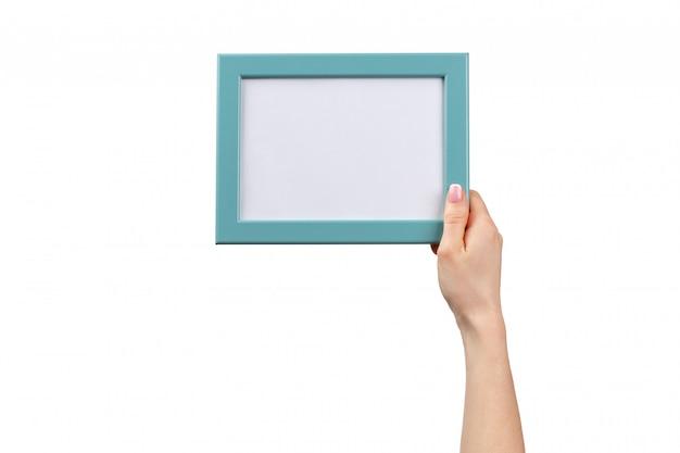 Kobieta wręcza trzymać fotografii ramę odizolowywająca na bielu
