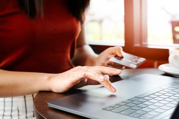 Kobieta wręcza trzymać kredytową kartę i używać laptop. zakupy online