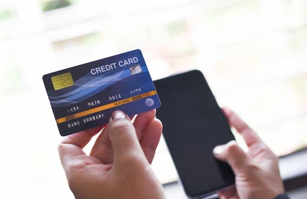 Kobieta wręcza trzymać kredytową kartę i używać smartphone dla online zakupy / ludzie płaci technologia pieniądze portfla online zapłatę w domu