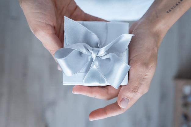 Kobieta wręcza trzymać prezenta pudełko z białym łękiem, zakończenie