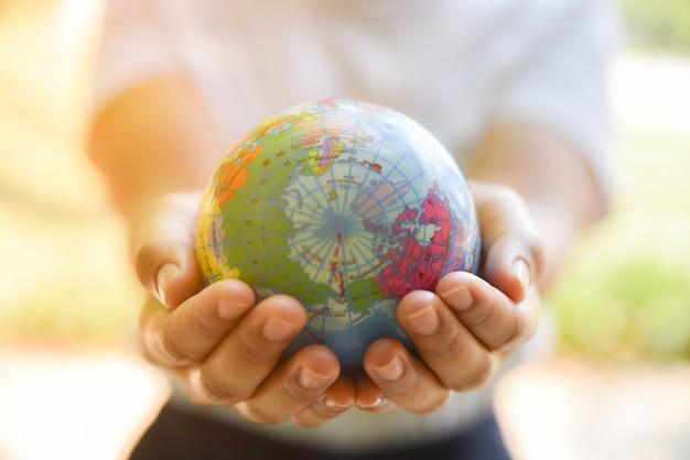 Kobieta wręcza trzymać światową piłkę na jej ręce z naturalnym zielonym tłem. koncepcja dzień środowiska naturalnego.