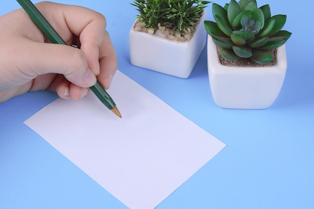 Kobieta wręcza writing na pustym papieru prześcieradle z piórem