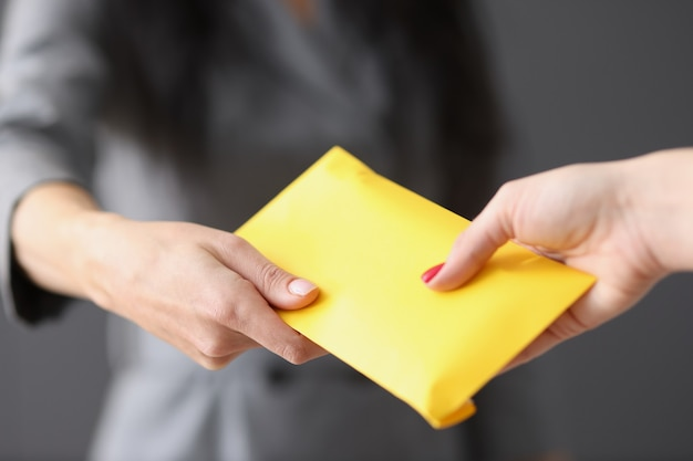 Kobieta wręcza żółtą zamkniętą kopertę z pieniędzmi na oszustwa pracownicze i składki w kopertach