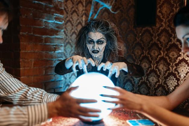 Kobieta wróżbita woła duchy nad kryształową kulą, czary.