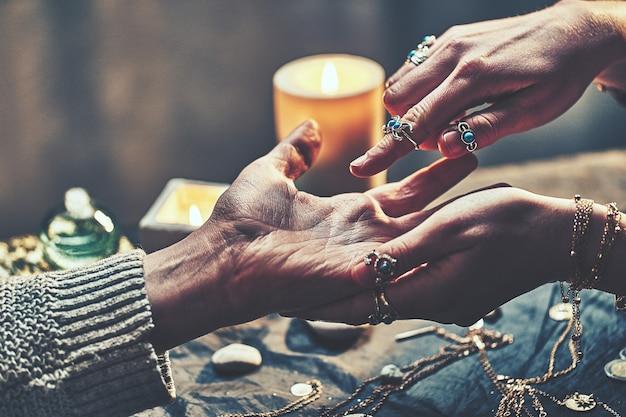 Kobieta wróżki nosząca srebrne pierścienie z turkusowym kamieniem i bransoletki czyta linie dłoni