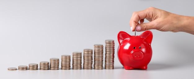 Kobieta wrzuca monetę do skarbonki. koncepcja inteligentnego przechowywania oszczędności