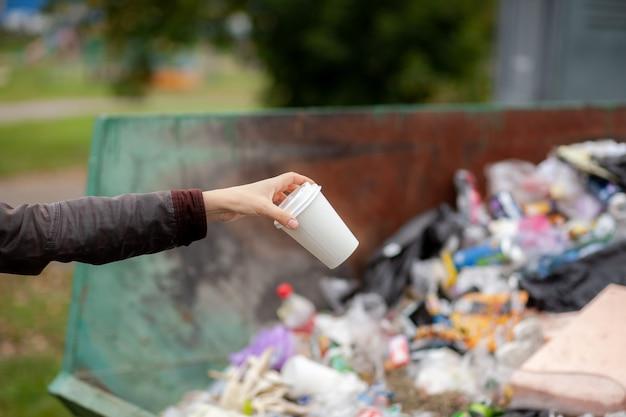 Kobieta wrzuca tekturową szklankę do kosza na surowce wtórne. dbanie o czystość miasta i środowiska. duży kosz na śmieci w publicznym parku