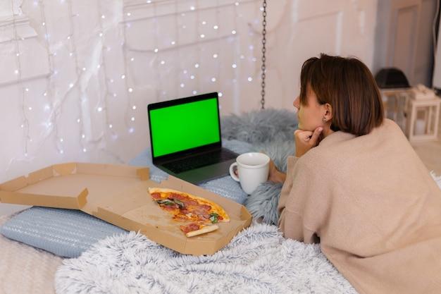 Kobieta wschód fast food pizza z dostawy na łóżku w sypialni w domu w czasie bożego narodzenia nowego roku.