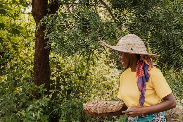 Kobieta wsi gospodarstwa kosz z orzeszkami ziemnymi
