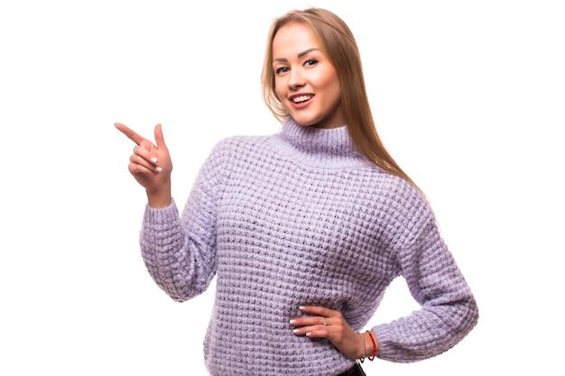 Kobieta, wskazując na bok stojący w pełnej długości - na białym tle na białej ścianie.