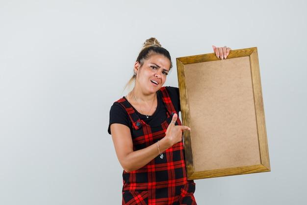 Kobieta, wskazując na pustą ramkę w fartuszek i patrząc zdezorientowany. przedni widok.