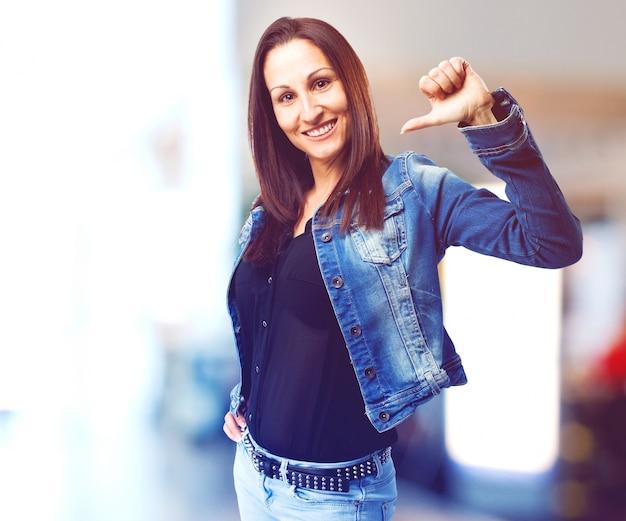 Kobieta, wskazując na siebie z kciukiem