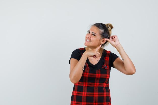 Kobieta, wskazując na ucho w fartuszek, widok z przodu.